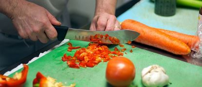 Hands slicing peppers